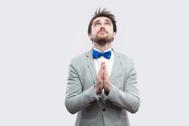 神は私を助けてください。カジュアルな灰色のスーツ、手のひらの手で立っている青い蝶ネクタイ、彼を助けたり許したりするように神に懇願する心配しているハンサムなひげを生やした男。明るい灰色の背景に分離された屋内スタジオショット。
