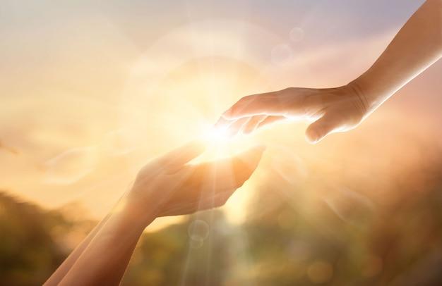 일몰 배경에 흰색 십자가와 하나님의 도움의 손길.