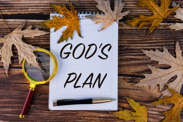 God's plan, the text is written in a white notebook with autumn maple leaves and old boards.