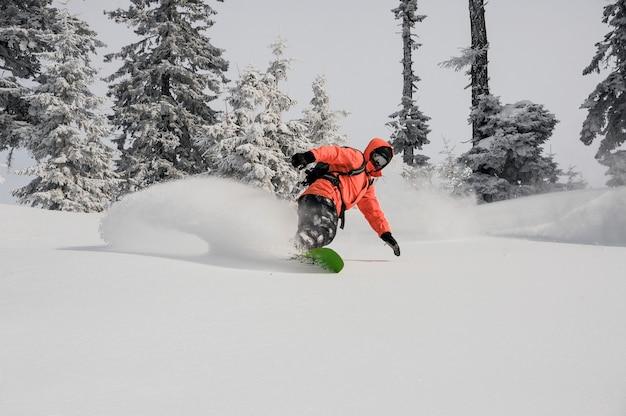 モミの木に囲まれたパウダーマウンテンヒルに乗るスノーボーダー。グルジア、goderdziでのスノーボード