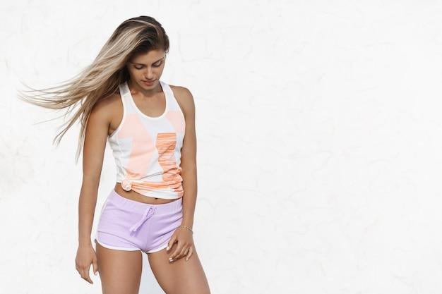 Goegeous 운동 무두질 백인 여자 좋은 모양, 스포츠 반바지를 입고 조깅 후 만족 휴식 미소 아래를 내려다 보면서