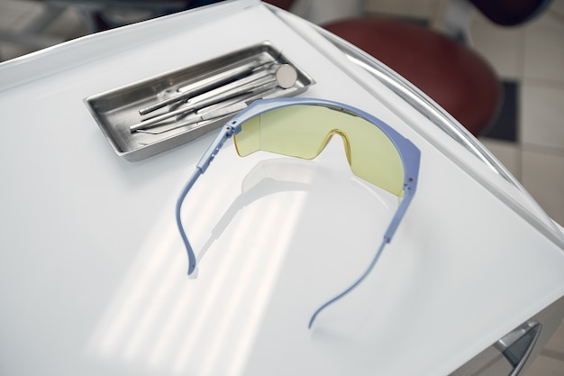 Goggles in the dentist's office.the tools lie on a tray.preparing the dentist before admission