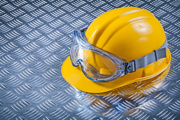 Goggles hard hat on fluted metal background construction concept
