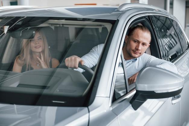 Возвращаться. позитивный менеджер, показывающий покупательнице особенности нового автомобиля