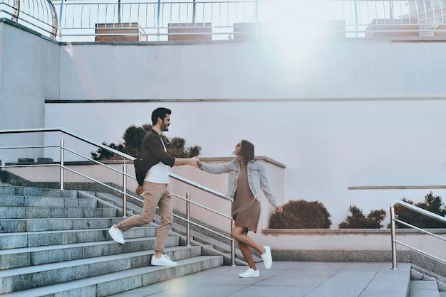 함께 미쳐갑니다. 잘 생긴 남자와 손을 잡고 젊은 매력적인 여자의 전체 길이