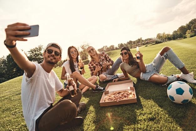 一緒に夢中になる。屋外で食べ物や飲み物を楽しみながら自分撮りをしているカジュアルな服装で若い笑顔の人々のグループ