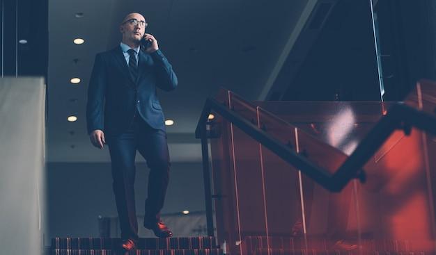 Спускаясь по лестнице, по телефону разговаривает бизнесмен, одетый в строгий деловой костюм.