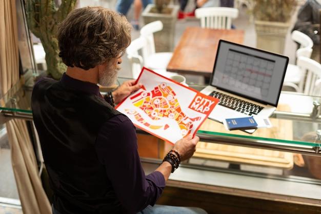 Собирается на прогулку. сосредоточенный турист сидит за столиком в кафе со своим ноутбуком и документами на нем и рассматривает карту города в кафе.