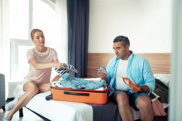 Иду домой. сосредоточенная супружеская пара сидит на кровати перед окном и собирает одежду перед выходом из отеля.