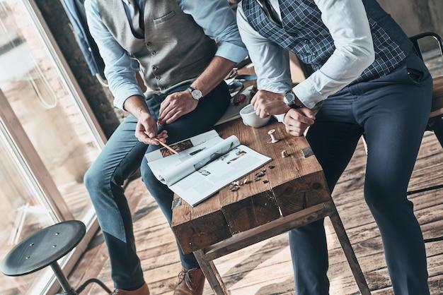 세부 사항을 진행합니다. 워크샵에서 시간을 보내는 동안 디자인을 선택하는 두 남자의 상위 뷰를 닫습니다