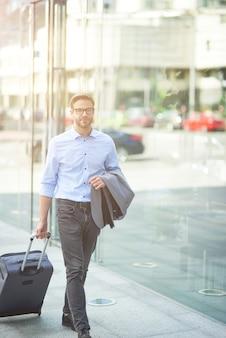 Идущий к терминалу аэропорта вертикальный снимок молодого уверенного бизнесмена, идущего по улицам города