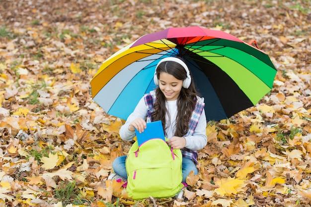 Собираюсь читать книгу. счастливое детство. обратно в школу. девушка в гарнитуре с рюкзаком расслабиться в парке. наслаждайтесь падением в лесу. слушать музыку. онлайн-курсы обучения. осенний малыш под зонтиком.