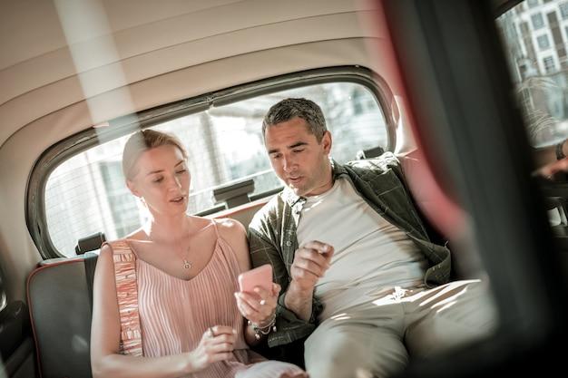 데이트하러 갑니다. 차 뒷좌석에 앉아 스마트폰 지도에서 목적지를 바라보며 웃고 있는 부부.