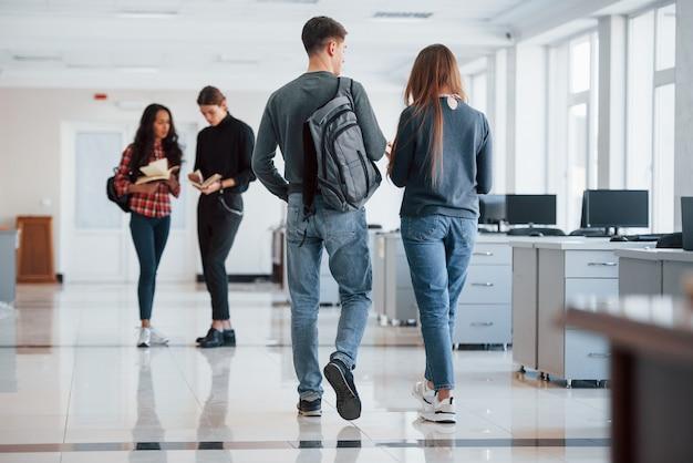 Собираюсь на встречу. группа молодых людей, идущих в офисе во время перерыва