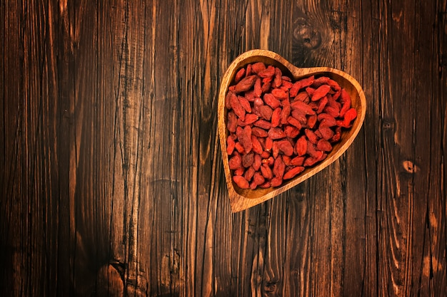 Goji berries in a heart-shaped wooden bowl over wooden background.