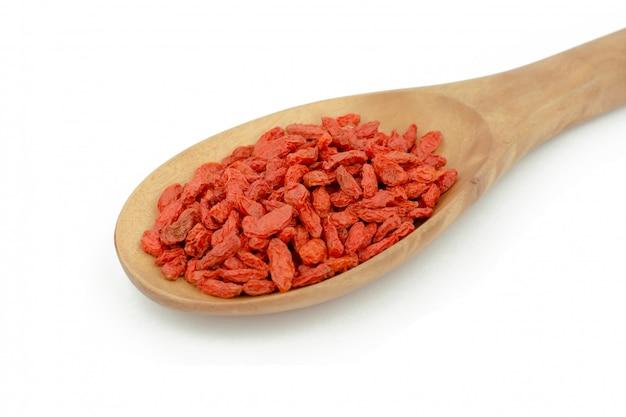 Goji berries in wood spoon on white background