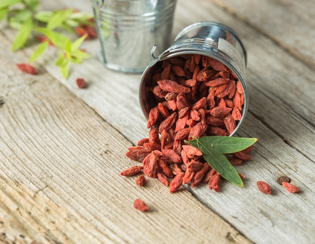 Goji in bowl on wood table. top view of fresh goji in scoop and bowl.