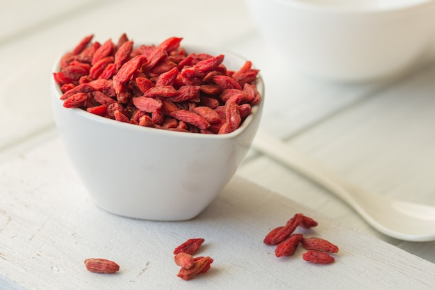 Goji in bowl on wood table.