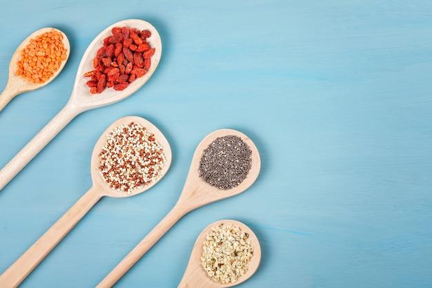 さまざまなスーパーフードgojiベリー、キノア、チア、大麻の種子、青の背景にランチル。ビーガン、ベジタリアン、健康的な食事、オーガニック製品のコンセプト
