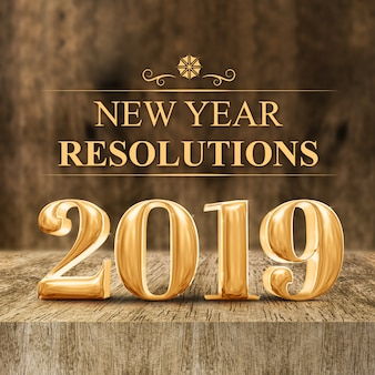 Gold 2019 new year resolutions at wooden block table