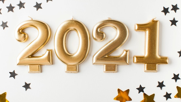 Gold 2021 candles on a white surface