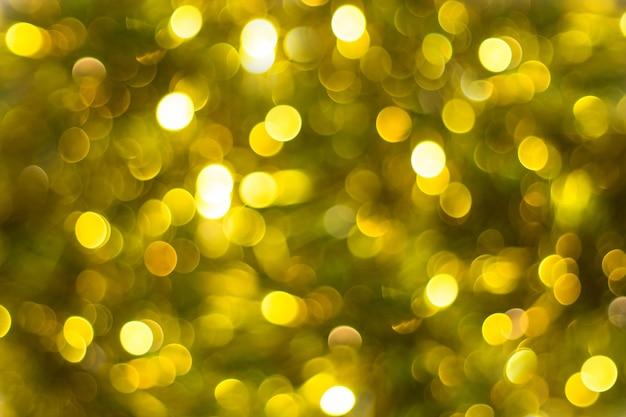 ボケ味の焦点ぼけライトとゴールドの抽象的な背景。
