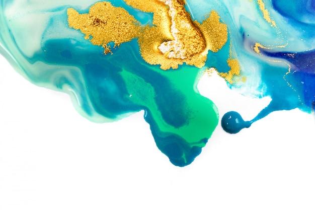 Золото и синие смешанные чернила забрызгали на фоне белой бумаги