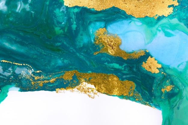 ゴールドとブルーの混合インクがホワイトペーパーの背景に飛び散った。