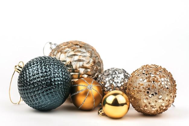 Золотые и синие блестящие рождественские шары на белом изолированы.