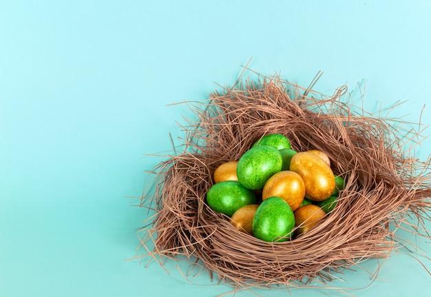 Яйца золотого и зеленого цвета в гнезде. понятие пасхи