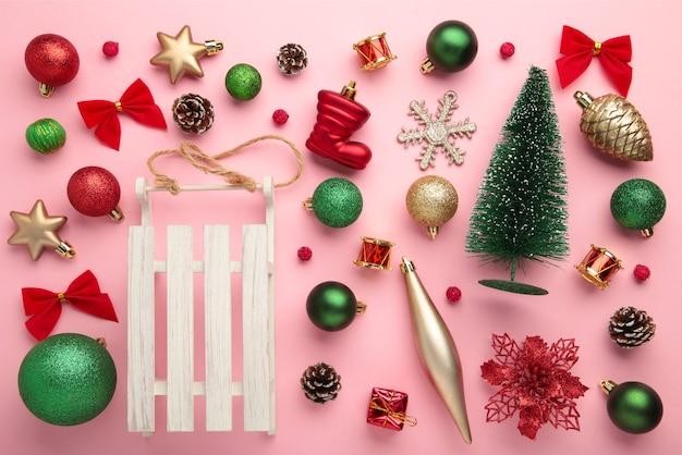 ピンクの背景、上面図、フラットレイの金と赤のクリスマスの装飾。新年の構成