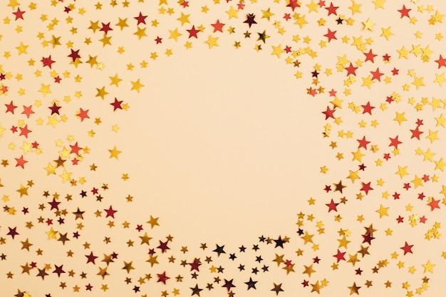 Золотое и красное конфетти в форме звезды на бежевом бумажном фоне. праздничный праздничный фон. поздравления с днем рождения рождество новый год. плоская планировка, вид сверху, копия пространства.