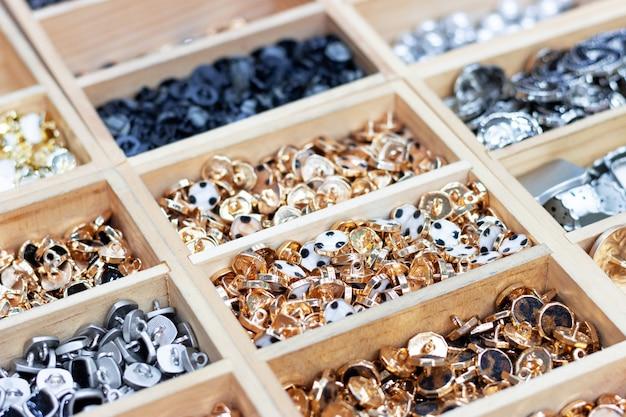 Золотые и серебряные пуговицы лежат в деревянных пазах, вид сбоку