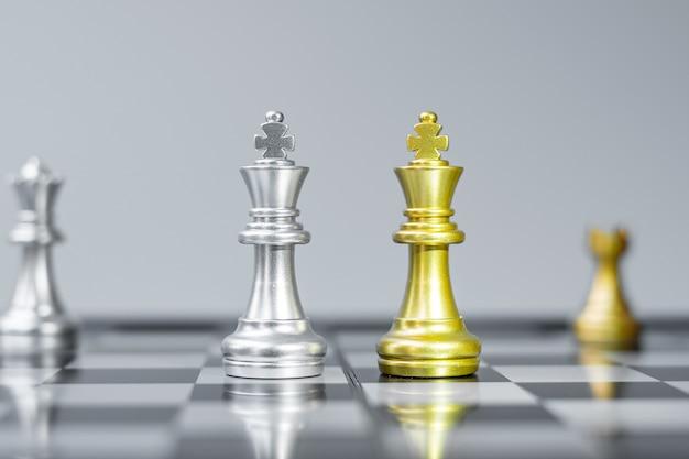Золотая и серебряная фигура шахматного короля на шахматной доске