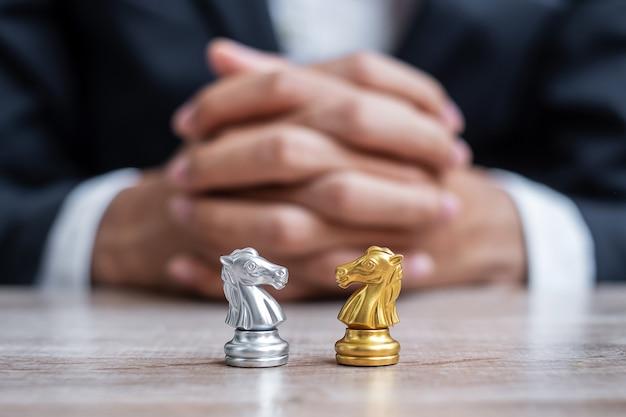 사업가 관리자 배경으로 금색과 은색 체스 나이트 그림.