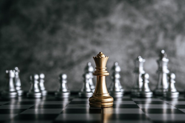 Золотые и серебряные шахматы на шахматной настольной игре для концепции лидерства в метафоре бизнеса