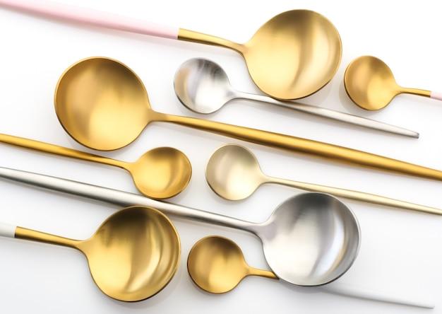 Золотые и серебряные ложки, чайные ложки на белом фоне