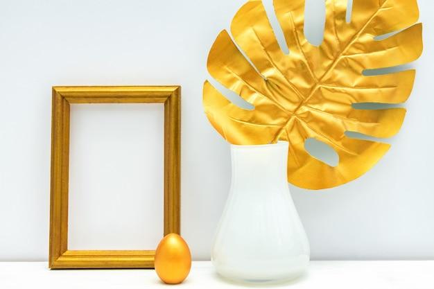 Золотой и белый интерьер. пустая фоторамка, расписное яйцо и лист монстеры.