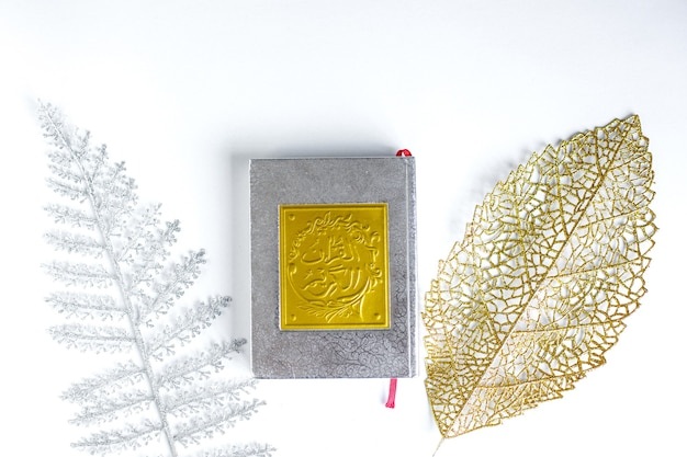 Gold arabic on holy quran with silver and gold leaves on white background