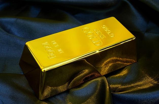 Gold bar 1 kg on smooth elegant black silk fabric luxury cloth background