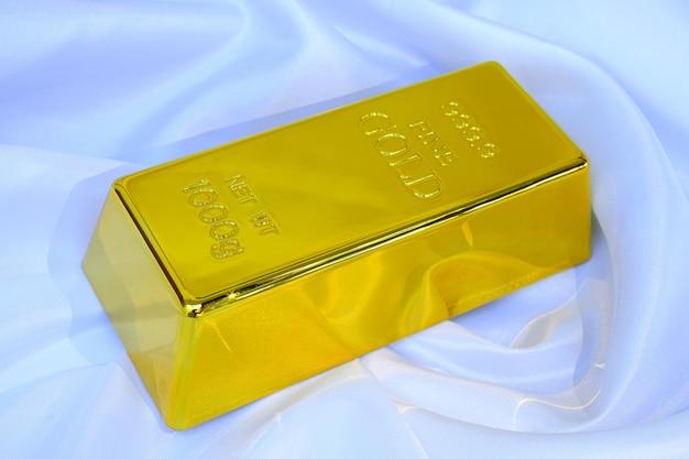 Gold bar 1 kg on smooth elegant white silk fabric luxury cloth background