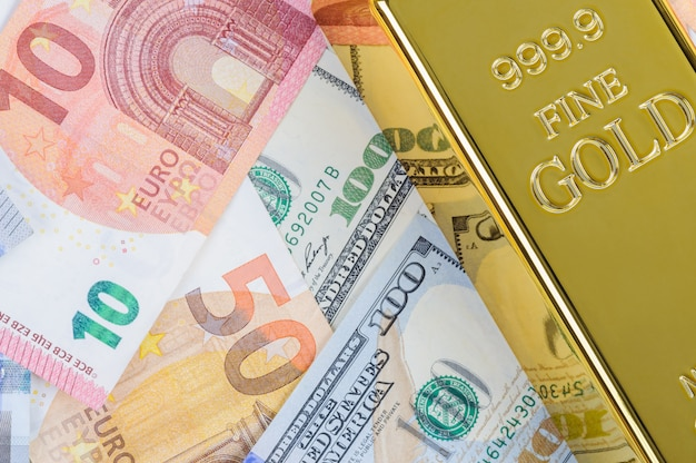 Gold bar ingot bullion against the background of dollar and euro bills.