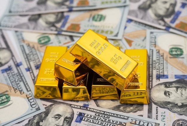 Gold bars on 100 new us dollar banknotes. business and finance concept