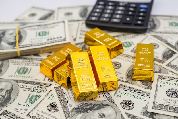 Золотые слитки и калькулятор на 100 новых банкнот доллара сша. концепция бизнеса и финансов