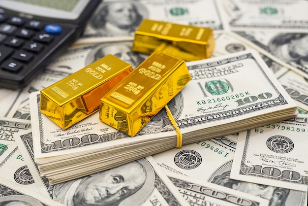 100 개의 새로운 미국 달러 지폐에 금괴 및 계산기. 비즈니스 및 금융 개념
