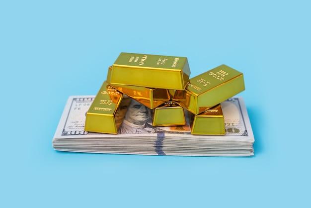 Золотые слитки и доллары на синем столе.