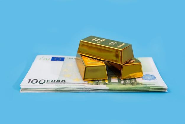 Золотые слитки и банкноты евро на синем столе. финансовое богатство или концепция сбережений.