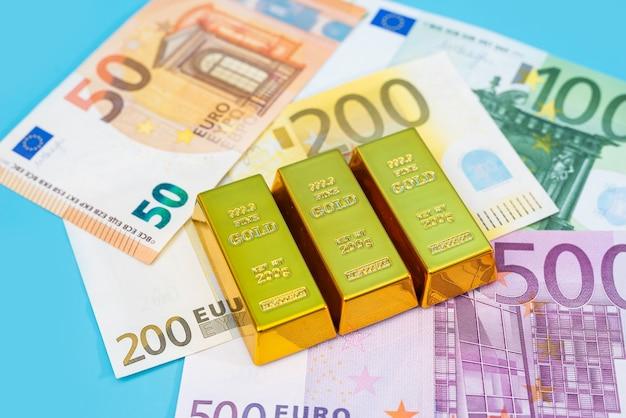 Золотые слитки и банкноты евро на синем столе.