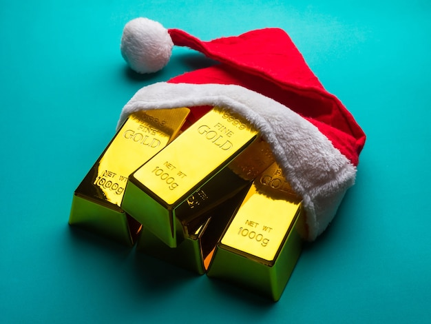 Gold bars as christmas present with santa hat on green background.