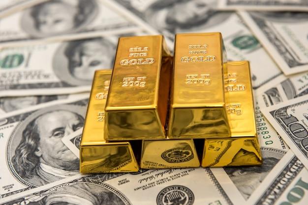 ドル紙幣の富の上に横たわる金の延べ棒地金